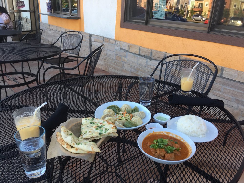 outdoor dining set with flat bread, dumplings, tikka masala and rice Takeout from Little Tibet - pi by mary w from yelp